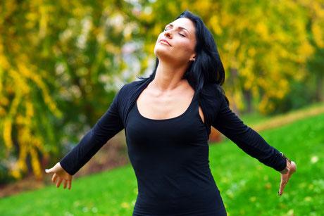 Eine Frau atmet tief durch. Dank einer Hypnosetherapie hat sie ihre Probleme im Griff.
