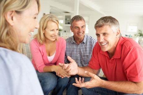 Ein Mann redet selbstsicher in gemütlicher Runde. Dank einer Hypnosetherapie stottert er nicht mehr.