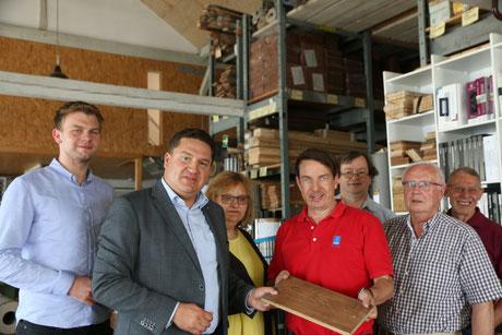 Marcus Held (2.v.l.) und Klaus Hagemann (2.v.r.) mit Gerhard (1.v.r.) und Gregor Hess (4.v.r.) sowie Mitarbeitern der Firma Fußboden Hess in der Produktion) Foto: privat