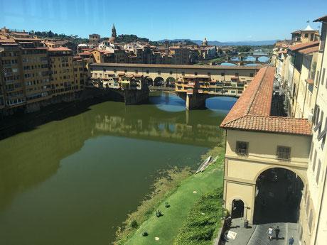 Blick aus der Galerie hinaus auf die berühmte alte Brücke Ponte Vecchio. Als einzige Brücke wurde sie von den Deutschen 1944 verschont und noch heute säumt ein Juwelierladen den anderen auf dem Weg zum Palazzo Pitti