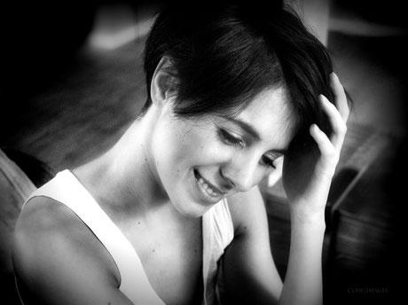 Schwarzweißportrait einer Frau, die lächelt und nach unten blickt