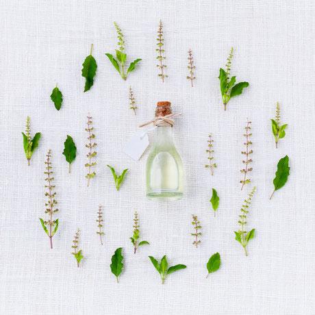 Bouteille d'huile essentielle sur nappe blanche entourée de plantes et fleurs. Image d'ambiance libre de droit