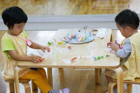 2歳児がキャンディとキャンディの間をモールで結びながら、キャンディレイを集中してつくっています