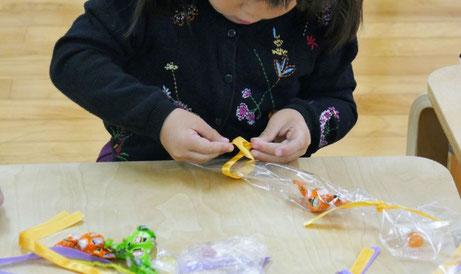 ハロウィンに向けて幼稚園児がキャンディレイをつくっています。キャンディとやンディの間をひもで結ぶ活動に集中しています。