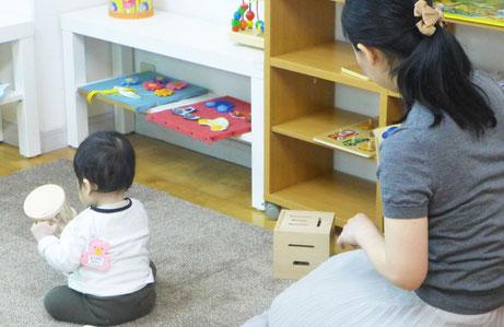 幼児教室のピッコロコース(0歳児)で、お母様がお子様の活動する様子を距離を置いて見守っています。