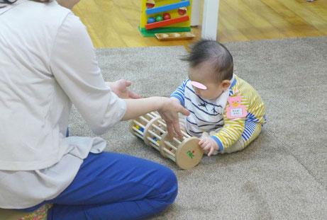 幼児教室のピッコロコースのモンテッソーリ活動で、8ヶ月の生徒が手を使った活動を集中して行っています。
