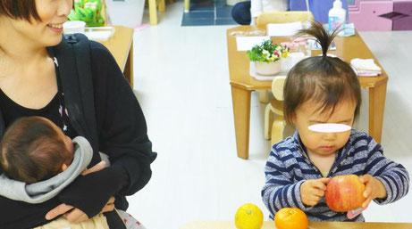 幼児教室のステッラコース(1歳児)で、お子様のモンテッソーリの活動をお母様が笑顔で見守っています。