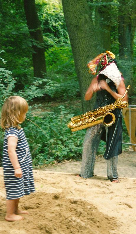 Anne Wiemann mit riesiger Vogelmaske auf dem Kopf und Bariton Saxofon vor dem Bauch. Sie spielt Piccolo, ein Kind steht gegenüber von ihr und schaut fasziniert zu