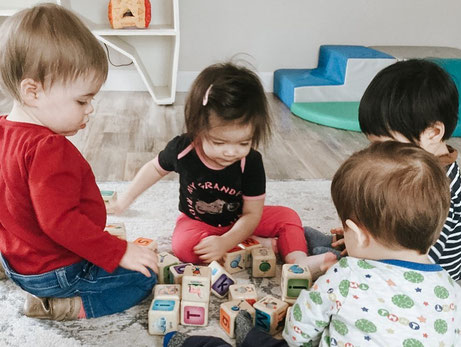Four toddlers playing with alphabet blocks together on the floor of the toddler room at The Wonder Playschool.