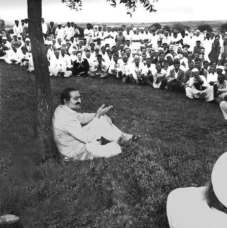 1954 , Meherabad, India ; Hitaker sitting with his hands together and wearing a dark suit.