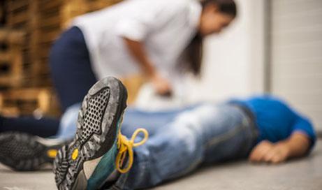 Verunfallter Mann liegt auf dem Boden und wird von einer Frau versorgt