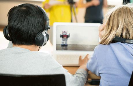 2 Kinder von hinten vor Notebook, auf dem ein Roboter zu sehen ist.