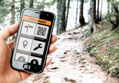 """Bild eines in der Hand getragenen Smartphones im Wald, auf dem ein Ausschnitt der App """"Actionbound"""" zu sehen ist."""