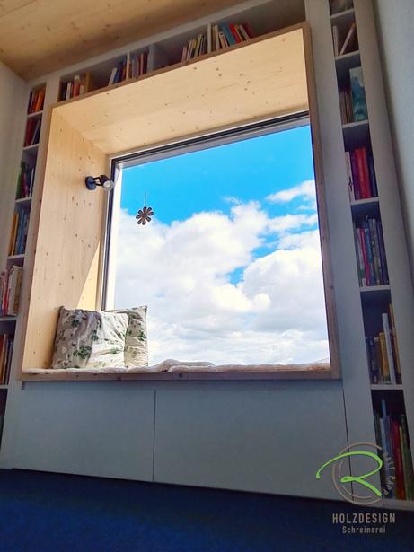 gemütliche Sitznische am Fenster mit Fichtenrahmen von Schreinerei Holzdesign Ralf Rapp in Geisingen, Sitzfenster mit integriertem Stauraum unter der Sitzbank  und Bücherregal als Rahmen