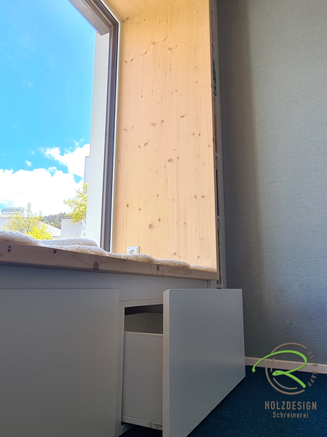 Unter Sitzbank integrierte Schubladen als Stauraum von Schreinerei Holzdesign Ralf Rapp in Geisingen, Sitzfenster mit Fichtenrahmen und integriertem Stauraum mit Schubladen und Bücherregal in weiß