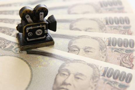 お金の上に置かれた映写機の置物