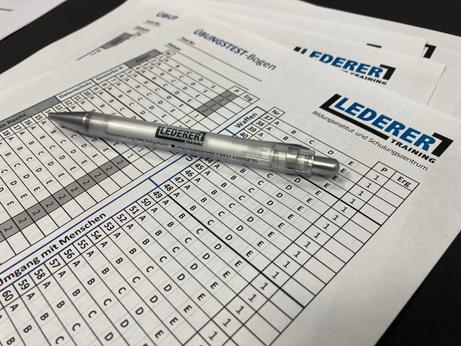 """Übungstest-Bögen für die IHK-Sachkunde-Prüfung nach § 34a GewO (im Volksmund: """"34a-Schein""""). Auf dem Tisch liegen mehrere Übungsbögen übereinander. Auf den Bögen und auf einem darüber liegenden Kugelschreiber steht das Logo von LEDERER_training."""