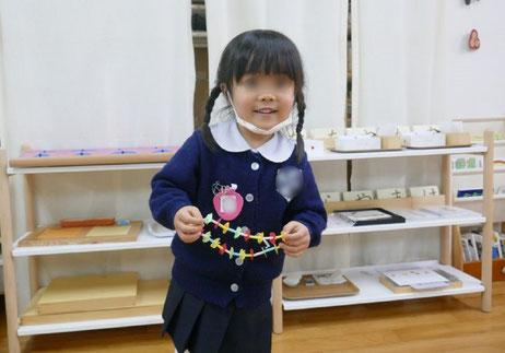 幼稚園児クラスのモンテソーリ活動で、年少の生徒が色の順序が整ったきれいなネックレスを作りました。