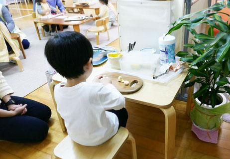 モンテッソーリの活動で、母子分離をした2才児が、バターナイフを使ってバナナを切る活動に集中して取り組んでいます。