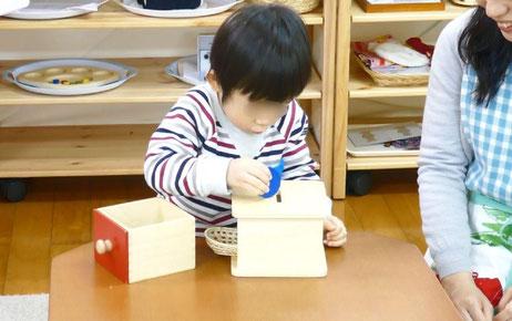 モンテッソーリの活動で、親子コースの1歳児が、コイン落としの新しいやり方を試しています。