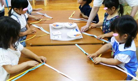 幼児教室の幼稚園児クラスで父の日のプレゼントを制作。腕時計のベルト用に短冊を三つ編みしました。