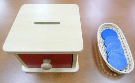 モンテッソーリの活動で、コインを木箱の溝から中に落とすコイン落としの活動を取り入れています。