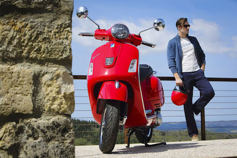 Rote Vespa 125 gts IGET ABS mit rotem Helm