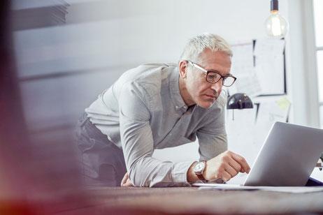Foto eines Mannes, der sich über ein Laptop beugt und dort etwas eintippt. Er ist im Internet unterwegs.