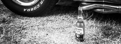 Bild zeigt eine vor dem geparkten Auto stehende volle Flasche Corona.