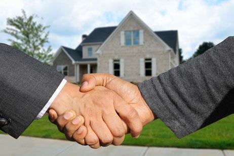 Männer geben sich nach einer Hauskaufberatung die hand