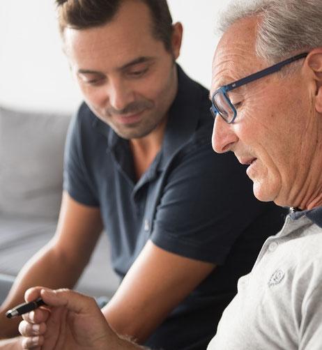 Älterer Herr berät sich mit seinem Betreuer