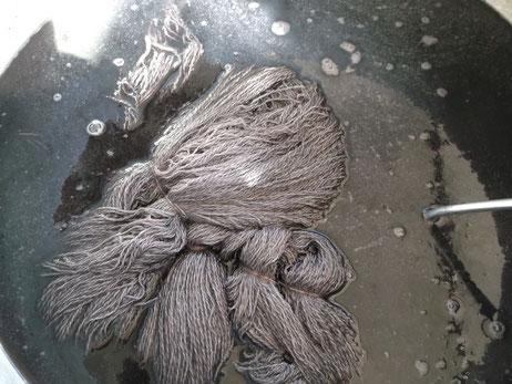 Wollgarne im Farbbad, gefärbt wird in Cochenille