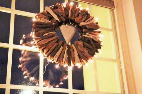 Treibholzkranz mit einem Holzherz und mit Lichterkette dekoriert