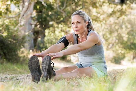 Eine sportliche Frau dehnt sich nach dem Joggen. Hypnose hat geholfen, die Motivation hochzuhalten.