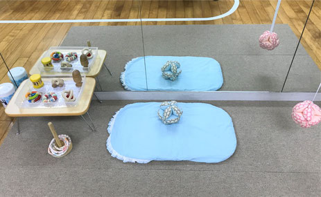 モンテッソーリ活動で、0歳児が活動しやすいように、鏡の前にトッポンチーノを敷き、低いテーブルに教具を配置しています。