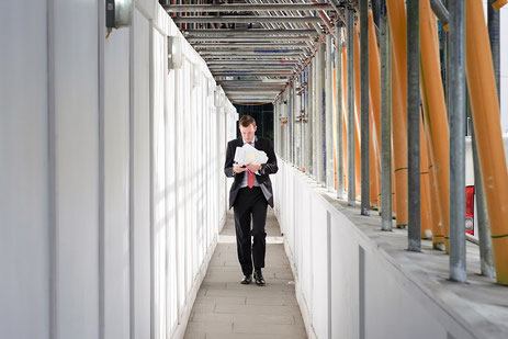 Mann im dunklen Anzug mit roter Krawatte geht durch eine Gebäudebaustelle
