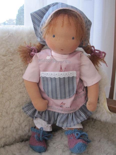 Licias Puppe ist bekleidet mit einem T-Shirt aus feinem rosa-weiß geringelten Bio-Jersey, einer Schürze aus altrosa Feenstoff (beide Stoffe Bio und GOTS-zertifiziert); Kopftuch sowie die Details an der Schürze sind ein graublauer Streifenstoffen von Westf
