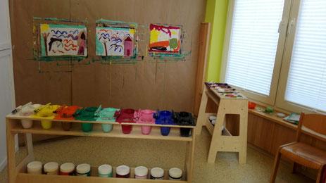 Ein eingerichteter Malplatz mit kleinen Palettentischen in einer integrativen Kindertagesstätte.  Drei Kinder können im Malprozess begleitet werden - ein besonderes Angebot für die Kinder mit den hochwertigen Gouachefarben frei zu gestalten