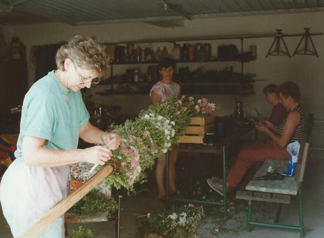 In einer Garage werden Buchsbüschel für die Blumenstange gebunden.