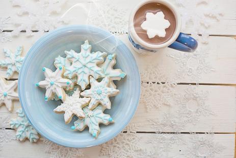 木製のテーブルに置かれたコーヒーカップとレースのリボンでまとめられたガーベラのブーケ。