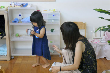 モンテッソーリ活動で、1歳児が小さなじょうろに水をくんで、こぼさないように慎重に運んでいます。