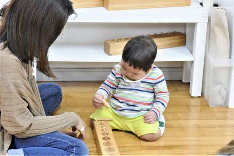 モンテッソーリの活動で、満1歳児がはめ込み円柱の活動。お母さまが見守りながら、子供の様子をしっかり観察しています。