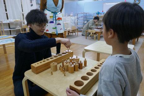 見学に来られた方が、年長児といっしょに感覚教具のはめ込み円柱を使ったゲームに挑戦し、楽しんでいます。