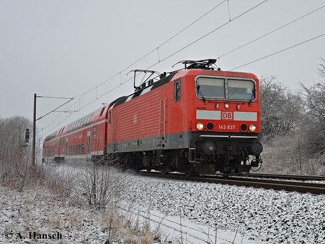 Am 23. Januar 2015 ist Grüna kurz vor Chemnitz von leichten Schneefällen weiß gepudert. Ein seltenes Bild, war der Winter 2014/2015 doch eher mild. 143 837-3 ist mit der RB Zwickau - Dresden gen Chemnitz unterwegs