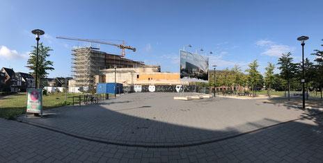Bild zeigt die Baustelle Kathrin-Türks-Halle mit Kran und Gerüst, am rechten Rand das Rathaus und den Stadtpark.