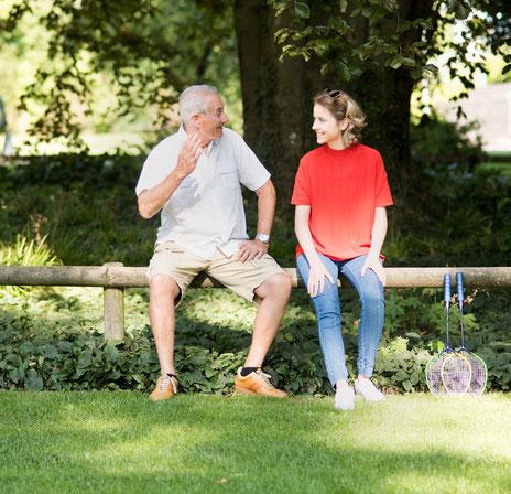 Älterer Herr erzählt junger Frau etwas im Park