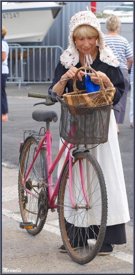 Femme avec son vélo, en tenue locale, coiffée de sa benaise, tricottant en attendant le retour des pêcheurs de sardine - Fête du Retour de la Pêche à la Sardine 2014 à Gujan-Mestras, Bassin d'Arcachon