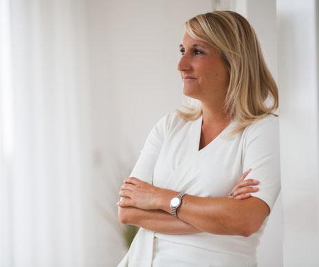 Kerstin Schmetzer lehnt an Wand und  denkt über Interventionen und Coaching Methoden nach