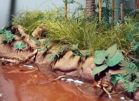 Uferböschung mit einzeln gefertigten Papierpflanzen.