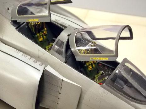 Geöffnte Cockpithauben mit den Besatzungsnamen und Blick auf Gurte und Armaturen.